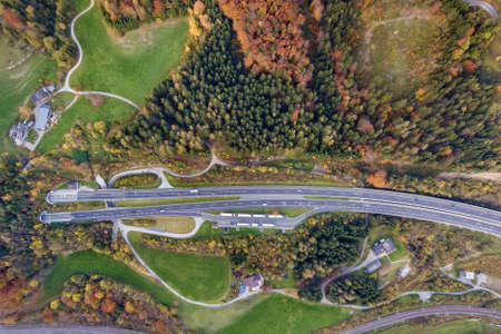 Top dawn aerial view of freeway speed road going out from undeground tunnel between yellow autumn forest trees in rural area.