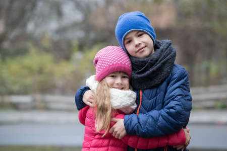 Two children boy and girl hugging each other outdoors wearing warm clothes in cold autumn or winter weather.