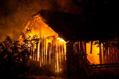 Casa in legno o fienile che brucia di notte.