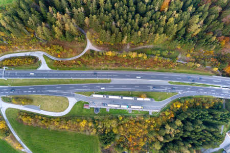Top dawn aerial view of freeway speed road between yellow autumn forest trees in rural area. Banco de Imagens