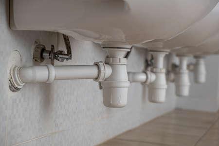 Cerca del desagüe del tubo de plástico blanco debajo del lavabo en el baño.