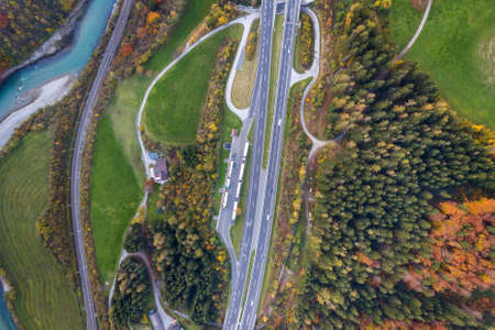 Top dawn aerial view of freeway speed road between yellow autumn forest trees and blue river.