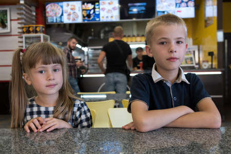 Children sitting in fast food restaurant behind empty table waiting for food.