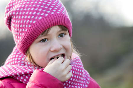 Pretty child girl in warm knitted winter clothes outdoors.