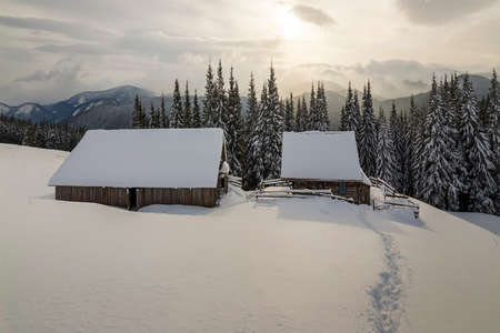 Winter mountain landscape. Old wooden houses on snowy clearing on background of mountain ridge, spruce forest and cloudy sky. Happy New Year and Merry Christmas card. Stock Photo