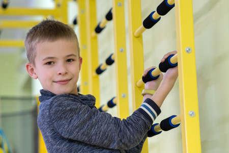 Jeune enfant garçon exerçant sur une échelle murale à l'intérieur d'une salle de sport dans une école.