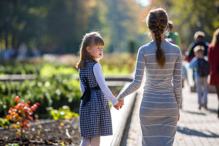 Back view of child girl and mother in dresses together holding hands on warm day outdoors on sunny background.