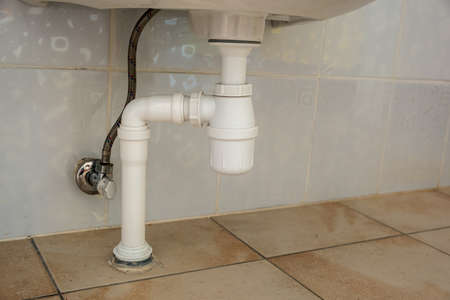 Close up of white plastic pipe drain under washing sink in bathroom.