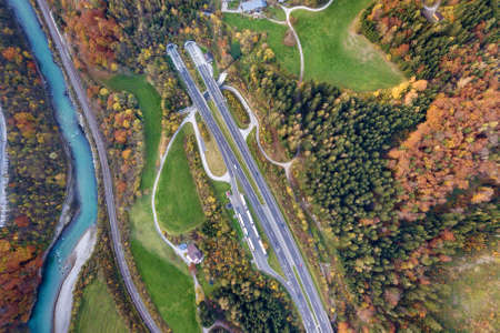 Top dawn aerial view of freeway speed road going out from undeground tunnel between yellow autumn forest trees and blue river.