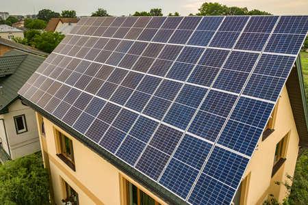 Vista aerea dall'alto del nuovo cottage moderno della casa residenziale con sistema di pannelli solari fotovoltaici blu brillante sul tetto. Concetto di produzione di energia verde ecologica rinnovabile.