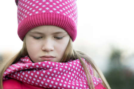 Sad child girl in warm knitted winter clothes outdoors.