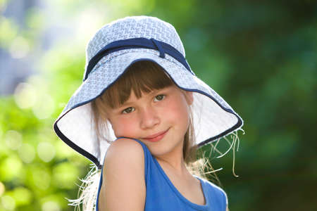 Close-up portrait of happy smiling little girl in a big hat. Child having fun time outdoors in summer.