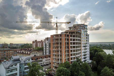 Apartment or office tall building under construction. Brick walls, glass windows, scaffolding and concrete support pillars. Tower crane on bright blue sky copy space background.