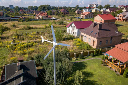 Aerial view of a new autonomous house with solar panels, water heating radiators on the roof and wind powered turbine on green yard. Stock Photo