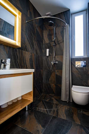 Interior of modern stylish bathroom with black tiled walls, curtain shower place and wooden furniture with wash basin and big illuminated mirror. Stock Photo