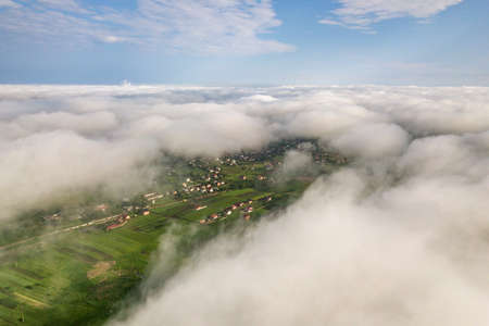 Aerial view of white clouds above a town or village with rows of buildings and curvy streets between green fields in summer. Countryside landscape from above. Stock Photo