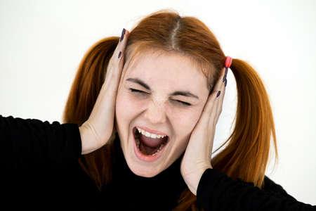 Close up portrait of pretty redhead teenage girl shouting like crazy.