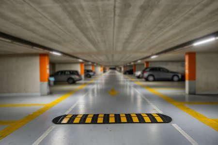 Contrassegni gialli con auto moderne sfocate parcheggiate all'interno di un parcheggio sotterraneo chiuso.