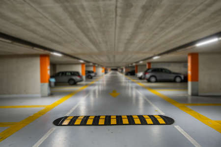 Gele markeringen met vage moderne auto's geparkeerd in een gesloten ondergrondse parkeerplaats.