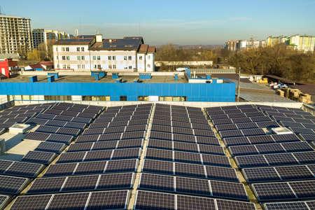 Widok z lotu ptaka wielu fotowoltaicznych paneli słonecznych zamontowanych na dachu budynku przemysłowego. Zdjęcie Seryjne