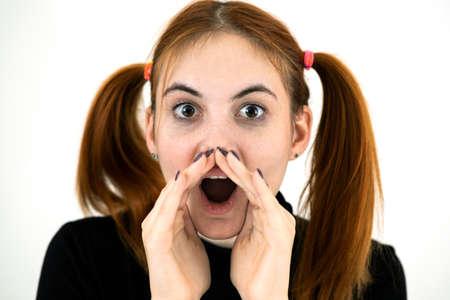 Close up portrait of pretty redhead teenage girl shouting.