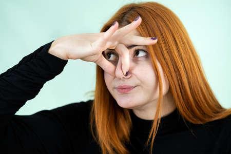Ragazza rossa graziosa divertente che mostra il segno di cattivo odore con le sue dita. Archivio Fotografico