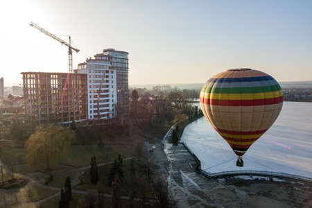 Colorful striped air baloon in city park.