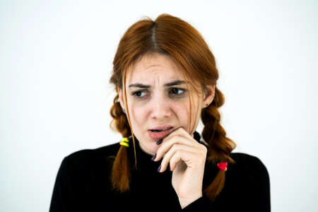 Portrait of serious young woman holding her hand to face thinking concentrated about something.