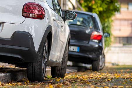Automóviles modernos estacionados en el lado de la calle de la ciudad en un distrito residencial. Vehículos brillantes aparcados junto a la acera. Concepto de infraestructura de transporte urbano.