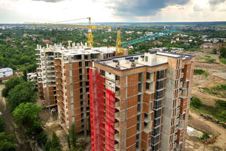 Aerial view of tower lifting crane and concrete frame of tall apartment residential buildings under construction in a city. Urban development and real estate growth concept. Stock Photo