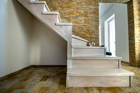 Stylish wooden contemporary staircase inside loft house interior. Modern hallway with decorative limestone brick walls and white oak stairs. Stockfoto