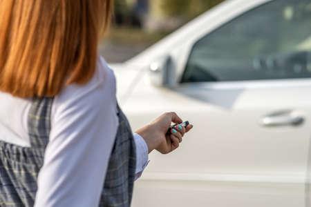 Redhead girl unlocking a car with wireless key. Banco de Imagens