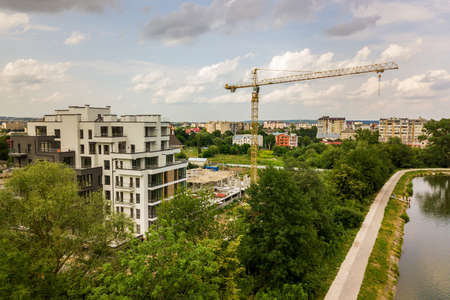 Aerial view of tower lifting crane and concrete frame of tall apartment residential building under construction in a city. Urban development and real estate growth concept. Stock Photo