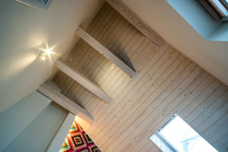 Wooden ceiling in a contemporary mansard room with attic window ob decorative planks surface.