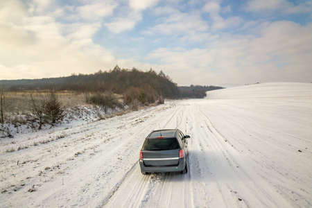 Family car driving on a dirt road in snow covered winter field.