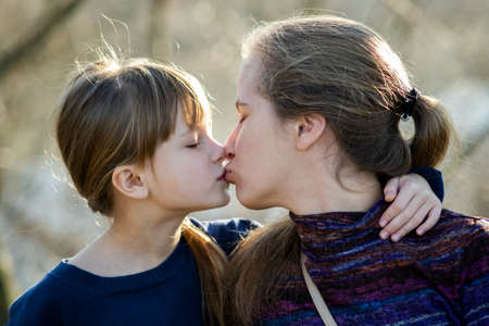 Young mom and her daughter girl together outdoors.