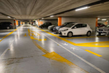 Yellow markings with blurred modern cars parked inside closed underground parking lot. 写真素材