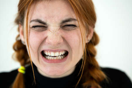 Close up portrait of angry redhead teenage girl.