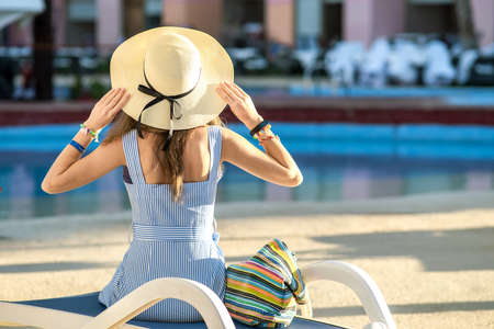 Young woman wearing light summer dress and yellow straw hat sitting outside near hotel swimming pool on summer sunny day. Reklamní fotografie