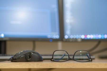 Closeup of protective glasses on an empty desk with blurred computer screen on background.