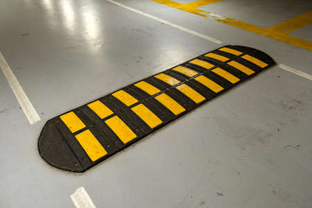 Striped black and yellow speed bump on a road. Stock Photo