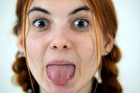 Closeup portrait of a funny redhead teenage girl with childish hairstyle sticking out her tongue isolated on white backround.