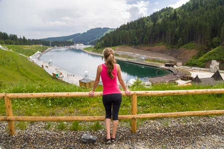Back view of a young sportive woman in fitness clothes standing outdoors near big lake in mountains enjoying nature view.