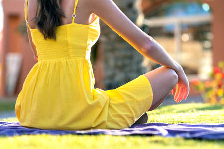 Young woman relaxing outdoors on sunny summer day. Happy lady sitting on green grass lawn daydreaming thinking. Calm girl enjoying fresh air relaxing and meditating.