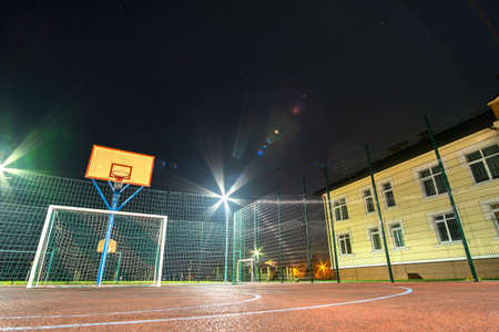Outdoors mini football and basketball court with ball gate and basket surrounded with high protective fence brightly illuminated with spotlight lamps at night. Banco de Imagens