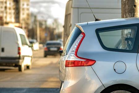 Modern cars parked on a side of a city street on a sunny day.