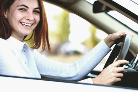 Young redhead woman driver behind a wheel driving a car smiling happily. Stock Photo