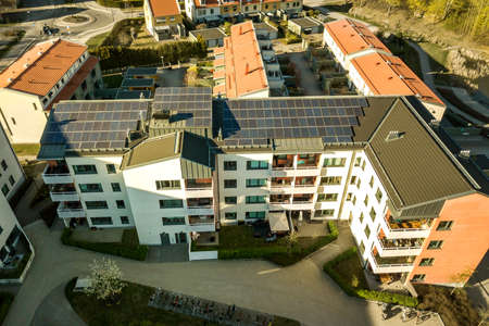 Aerial view of solar photovoltaic panels on a roof top of residential building block for producing clean electric energy. Autonomous housing concept. 版權商用圖片