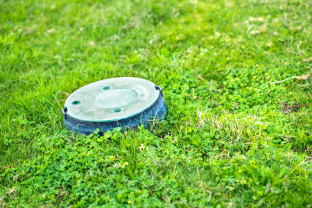 Closeup of green plastic pipe with cover on green grass lawn.