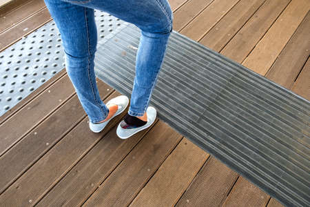 Female legs in denim jeans pants and light summer sneakers standing on wooden floow. Stock Photo